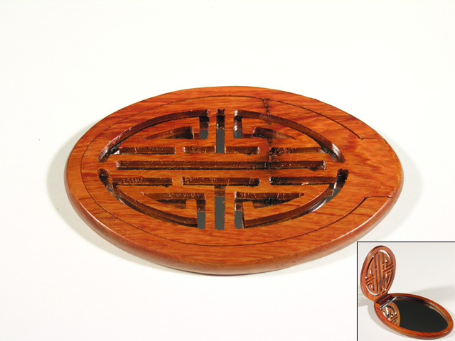 Pocket mirror with sculpted wood decoration